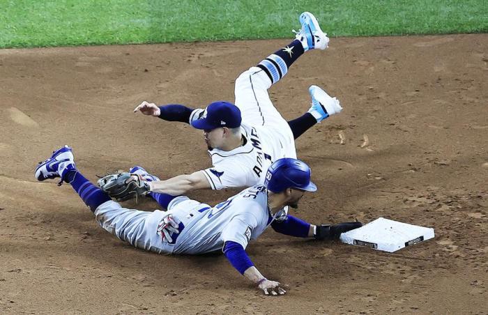 El jugador de los Dodgers de Los Ángeles Mookie Betts (abajo) logra llegar a base ante Willy Adames, de los Rays de Tampa Bay