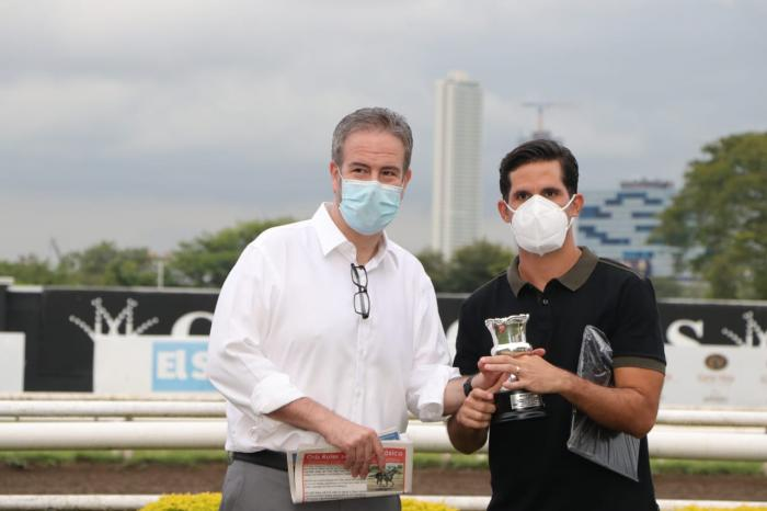 Alberto Paz Rodríguez jr. (izq.) entrega la copa del triunfo a Víctor Cardoze.