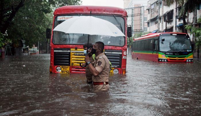 Un policía ayuda a un conductor a cruzar una calle inundada a causa de fuertes lluvias