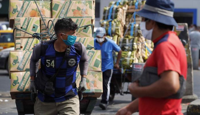 Fotografía de archivo del 9 de junio de 2020 que muestra trabajadores en el Mercado Mayorista de Frutas de Lima (Perú). Después de tres décadas de estabilidad económica en Perú, el flamante gobierno del izquierdista Pedro Castillo (2021-2026) plantea una