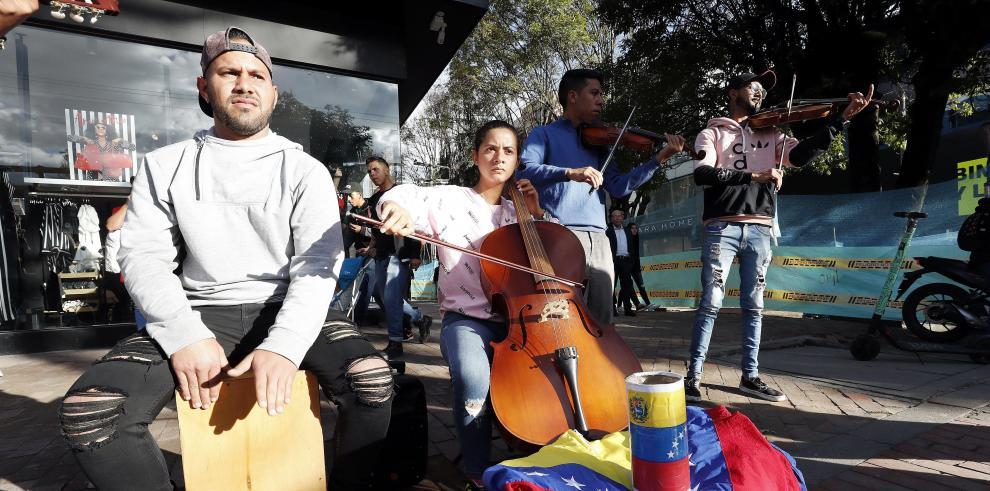 Fotografía fechada el 27 de septiembre de 2019 que muestra a los músicos venezolanos Omar Quintero (violín) y Alexis Velásquez (fagot), mientras actúan en un autobús de transporte público en Bogotá (Colombia).