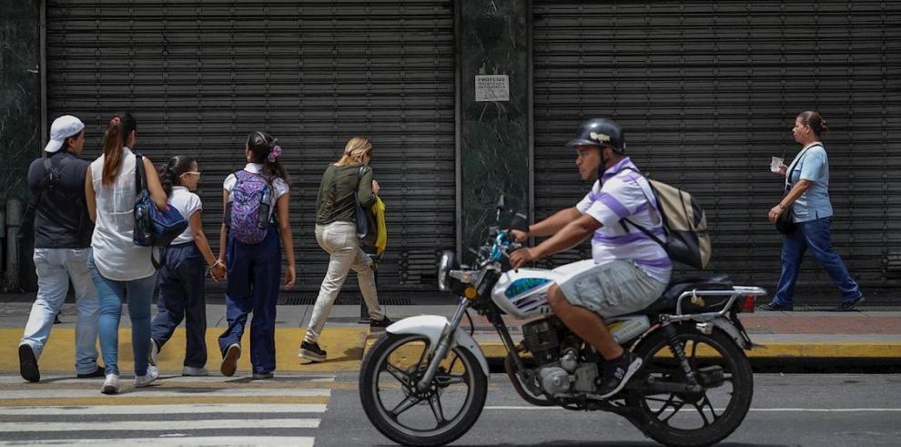 Personas caminan frente a un local comercial cerrado, en Caracas