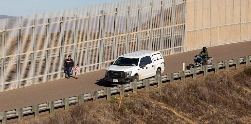 Una mujer migrante es detenida por la policía estadounidense en el muro fronterizo de la ciudad de Tijuana, en Baja California (México)