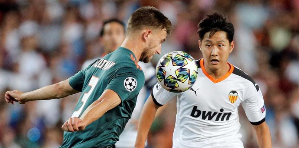 El defensa del Ajax, Joel Veltman (i), intenta controlar el balón ante el centrocampista coreano del Valencia, Kang-In Lee,