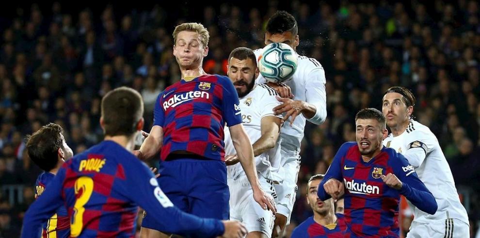 El delantero francés del Real Madrid Karim Benzema (c-d) pelea un balón aéreo con el centrocampista holandés del Barcelona Frenkie de Jong (c-i) durante el partido aplazado de la décima jornada de LaLiga Santander de fútbol que se disputa este miércoles e