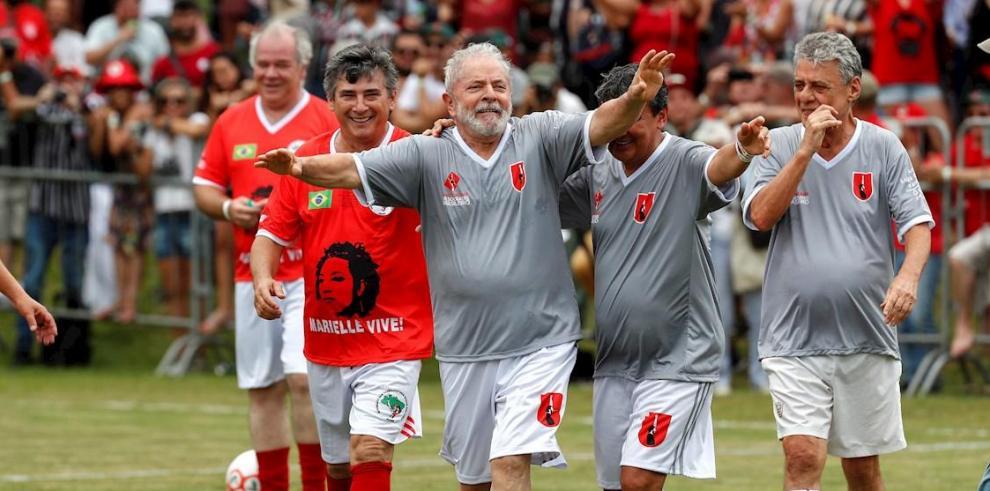El expresidente brasileño Luiz Inácio Lula da Silva (c) celebra su gol junto al compositor brasileño Chico Buarque (d) en un partido este domingo en la escuela rural Florestan Fernandes, en Guararema, estado de Sao Paulo (Brasil).