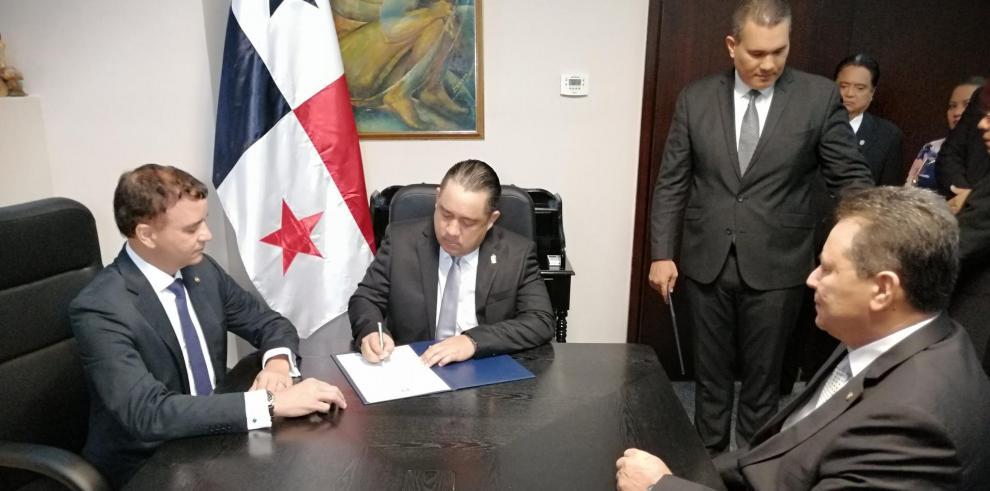 Momento en que el nuevo Contralor General,  Gerardo Solis , firma junto al nuevo subcontralor, Dagoberto Cortés, la toma de posesión de su puesto.