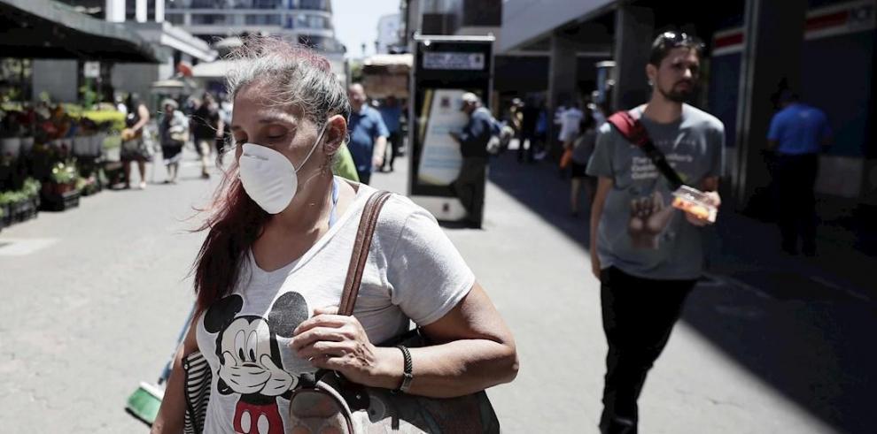 Una mujer usa una mascarilla este lunes mientras camina por las calles de San José (Costa Rica).
