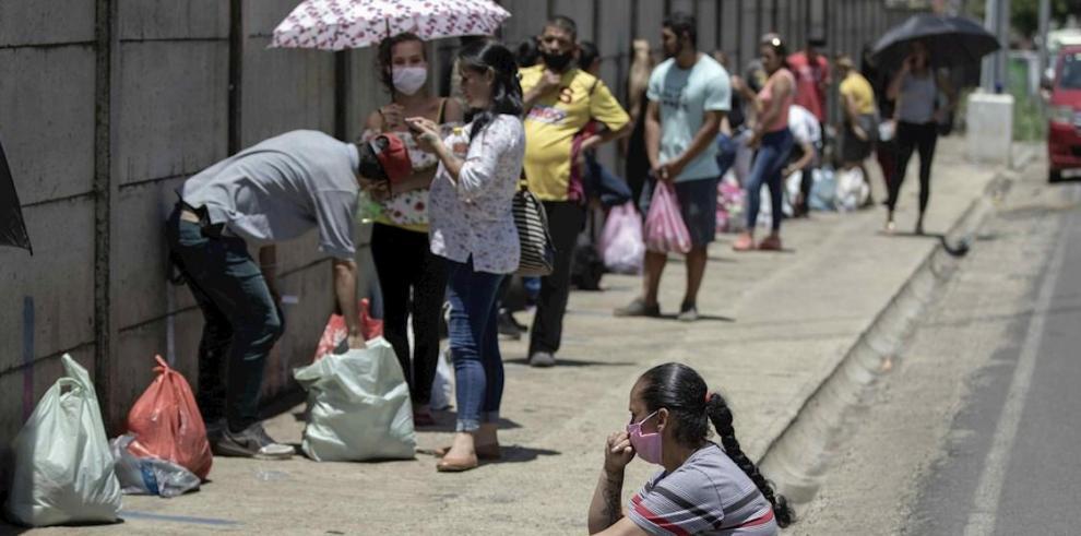 Varias personas con sus tapa bocas hacen fila para ingresar en horas de visita a un centro penitenciario en la provincia de Alajuela al oeste de San José (Costa Rica).