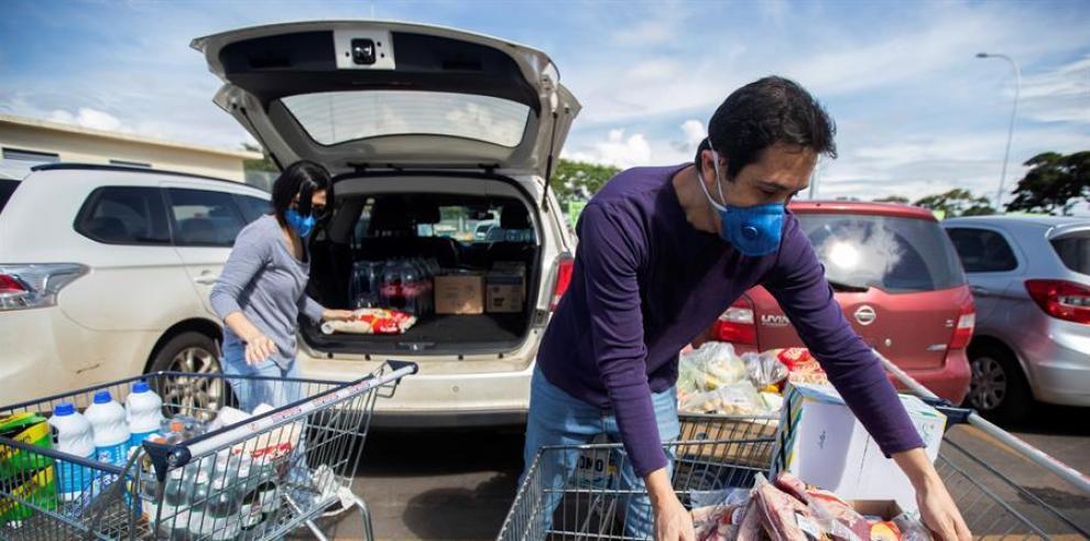 Una pareja con mascarillas organizan en su carro los víveres que compraron en una cadena de supermercados, en Brasilia