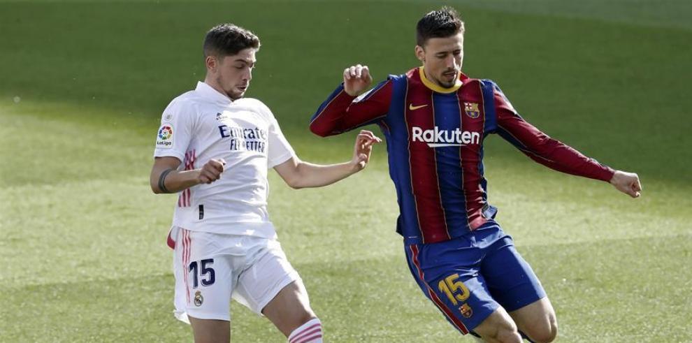 El defensa francés del Barcelona Clément Lenglet (d), intenta controlar el balón, ante la presencia del centrocampista del Real Madrid Fede Valverde