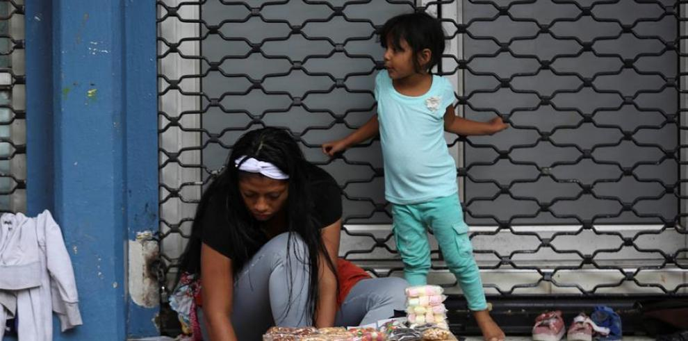 Una mujer junto a una niña vende dulces en Tegucigalpa