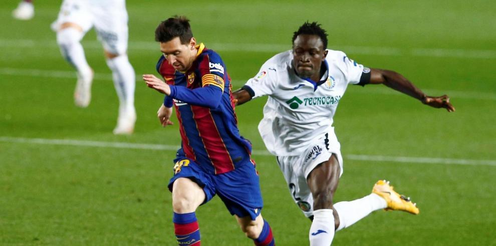 El delantero del FC Barcelona Leo Messi (i) escapa de Djene Dakoman, del Getafe, durante el partido de Liga en Primera División en el Camp Nou, en Barcelona.