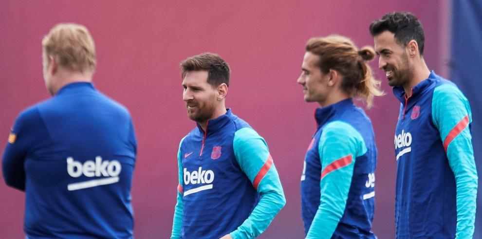 Los jugadores del FC Barcelona Leo Messi, Antoine Griezmann (2d), y Sergio Busquets (d), bajo la mirada del entrenador, Ronald Koeman (i), durante el entrenamiento que el equipo azulgrana ha realizado este lunes en la ciudad deportiva Joan Gamper