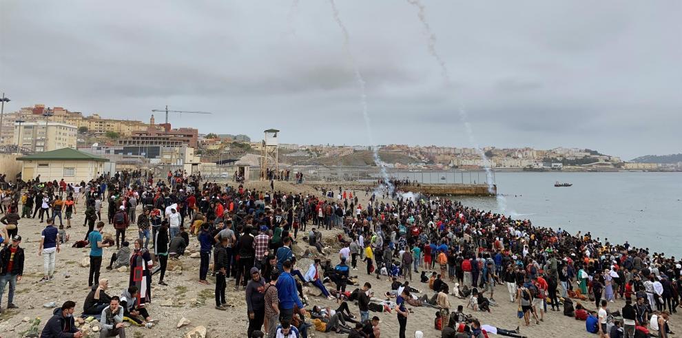Cientos de personas esperan en la playa de la localidad de Fnideq (Castillejos) para cruzar los espigones de Ceuta este martes en una avalancha de inmigrantes sin precedentes en España al registrarse la entrada en 24 horas de 5.000 personas