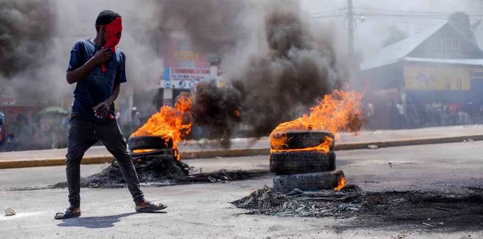 Un hombre observa varios neumáticos ardiendo durante una protesta este lunes, en Puerto Príncipe