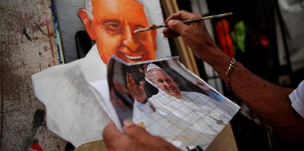 Un abuelo panameño pinta figuras gigantes del papa y camisetas con su cara