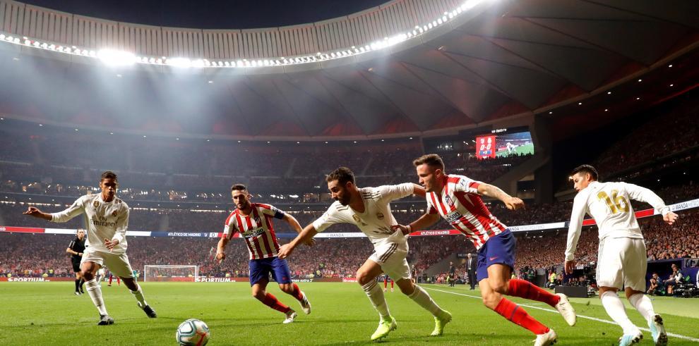 El defensa español del Real Madrid Dani Carvajal (c) disputa un balón con Saúl Ñíguez (2d), centrocampista español del Atlético de Madrid, durante el partido entre ambos equipos correspondiente a la séptima jornada de LaLiga, este sábado en el estadio Wan