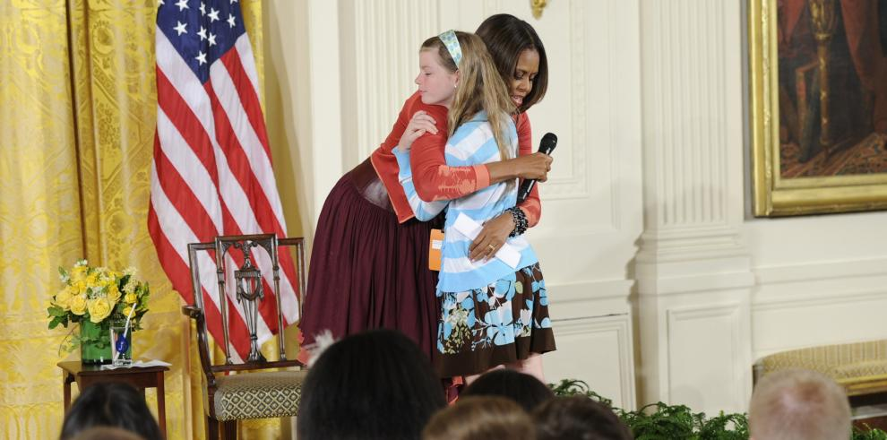 Una niña entrega a Michelle Obama el currículum de su padre desempleado