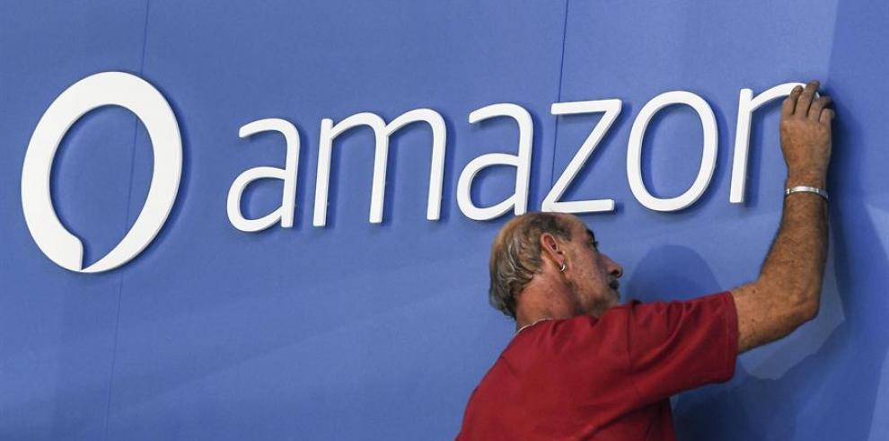 Un trabajador coloca el logo de Amazon.