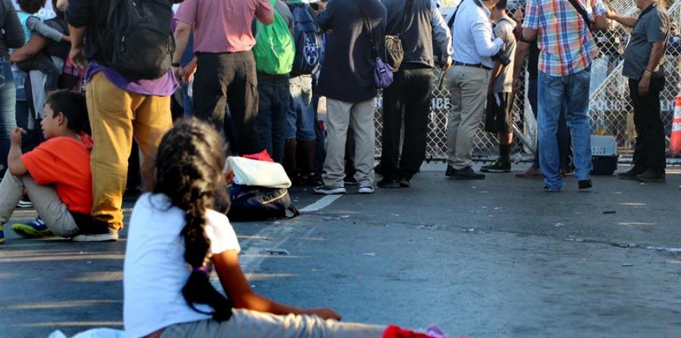 Migrantes centroamericanos esperan a las afueras de la estación fronteriza de Puente Nuevo (México)