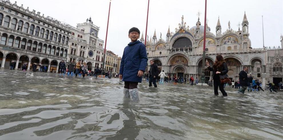 Un niño pasea por la inundada Plaza de San Marcos mientras las aguas comienzan a crecer, en Venecia (Italia).