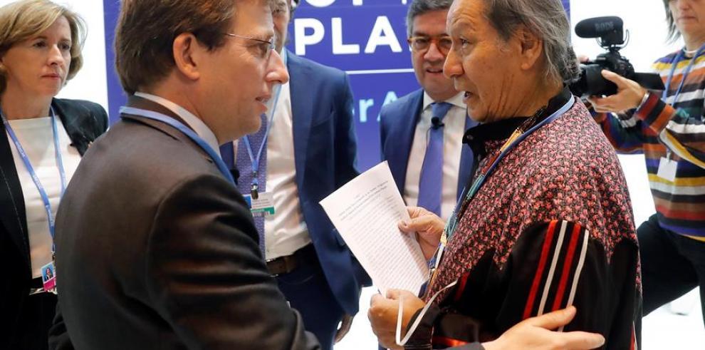 Un representante de de los pueblos indígenas (d) entrega un escrito en defensa de la Amazonia al alcalde de Madrid, José Luis Martínez-Almeida (i)