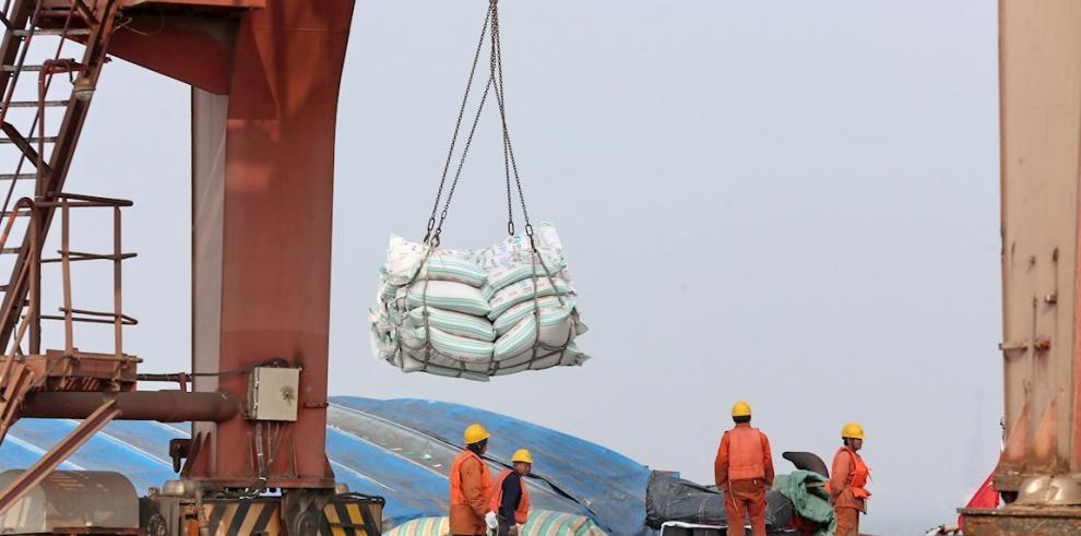 Unos operarios transportan bolsas de habas de soja en un puerto en Nantong (China).