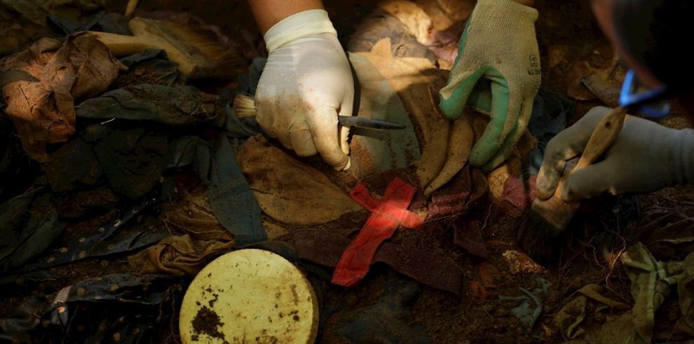 Antropólogos forenses examinan retazos de ropa durante la exhumación de restos humanos de víctimas de una masacre cometida por el Ejército salvadoreño en 1981.