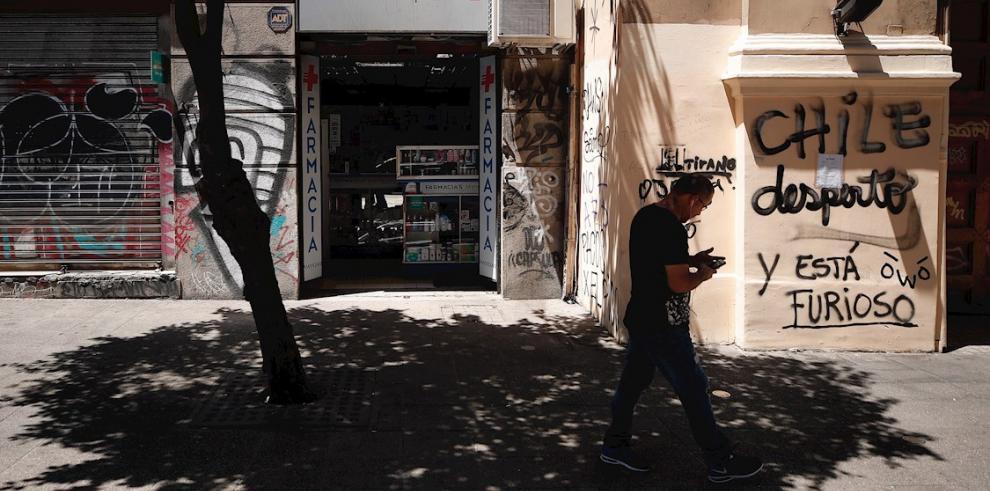 Un hombre camina frente a una farmacia este domingo en Santiago (Chile).