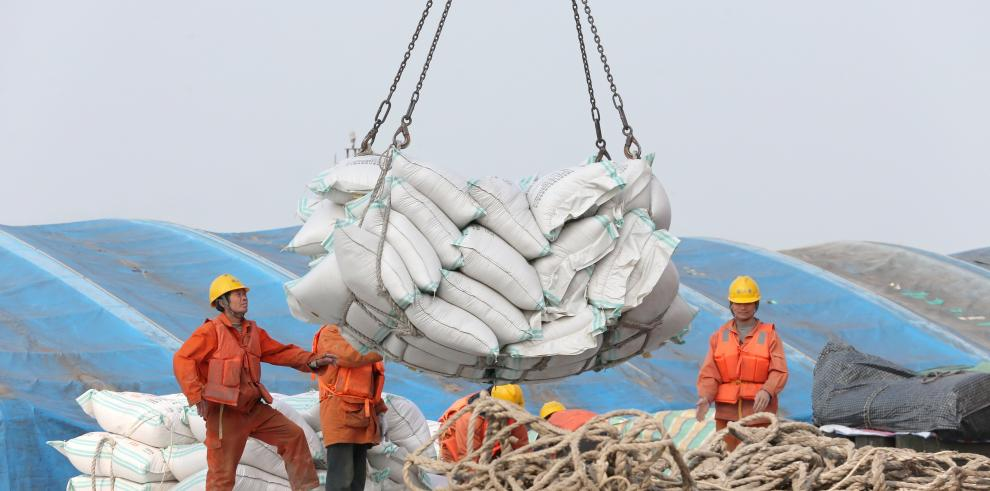 Fotografía de unos operarios mientras transportan bolsas de habas de soja en un puerto en Nantong