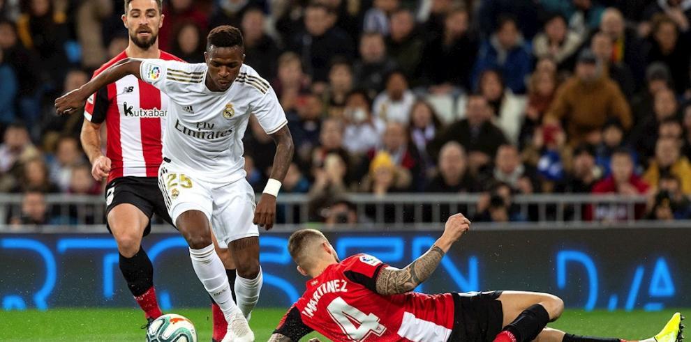 El delantero del Real Madrid Vinicius Junior (c) escapa de Íñigo Martínez (d), del Athletic de Bilbao, durante el partido de Liga en Primera División que disputaron en el estadio Santiago Bernabéu, en Madrid.