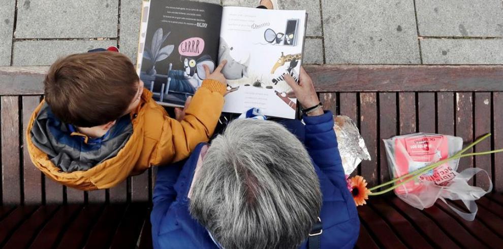 Un niño escucha a su abuela en la lectura de un libro.