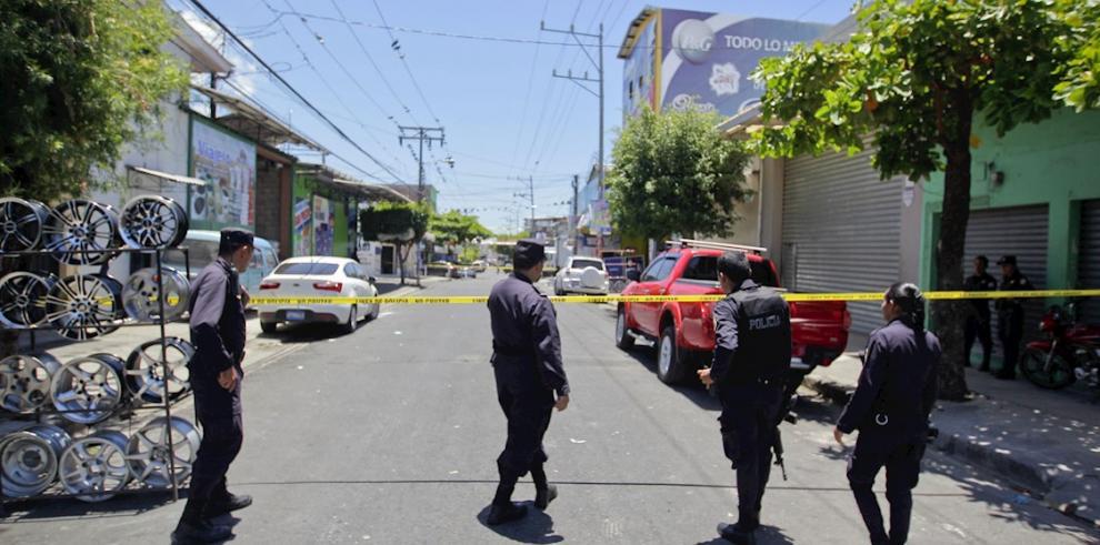 Agentes de la Policía Nacional Civil (PNC) investigan la escena de un crimen en San Salvador.