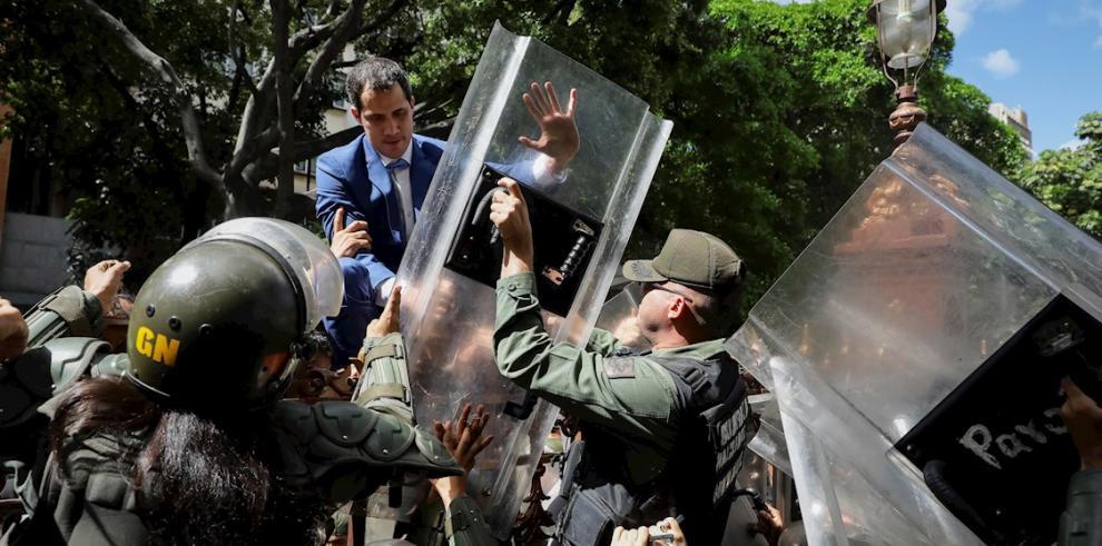El líder opositor venezolano Juan Guaidó fue registrado este domingo al trepar una reja, en un intento por entrar a la sede de la Asamblea Nacional, custodiada por la Policía y por miembros de la Guardia Nacional, que le impidieron su ingreso, en Caracas
