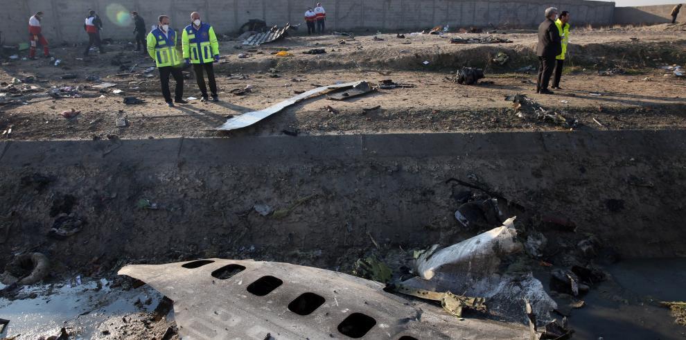 Miembros de los servicios de emergencia observan parte del fuselahe del Boeing 737 de la compañía ucraniana UIA que se estrelló en la madrugada del miércoles en Teherán.