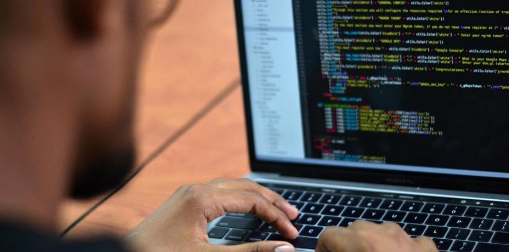 En la imagen, un hacker experto en ciberseguridad, revisa algunos códigos en su computador portátil.
