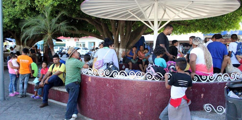 Migrantes, en su mayoría de origen hondureño, toman un descanso en una plaza de la ciudad de Tapachula en el estado de Chiapas (México).