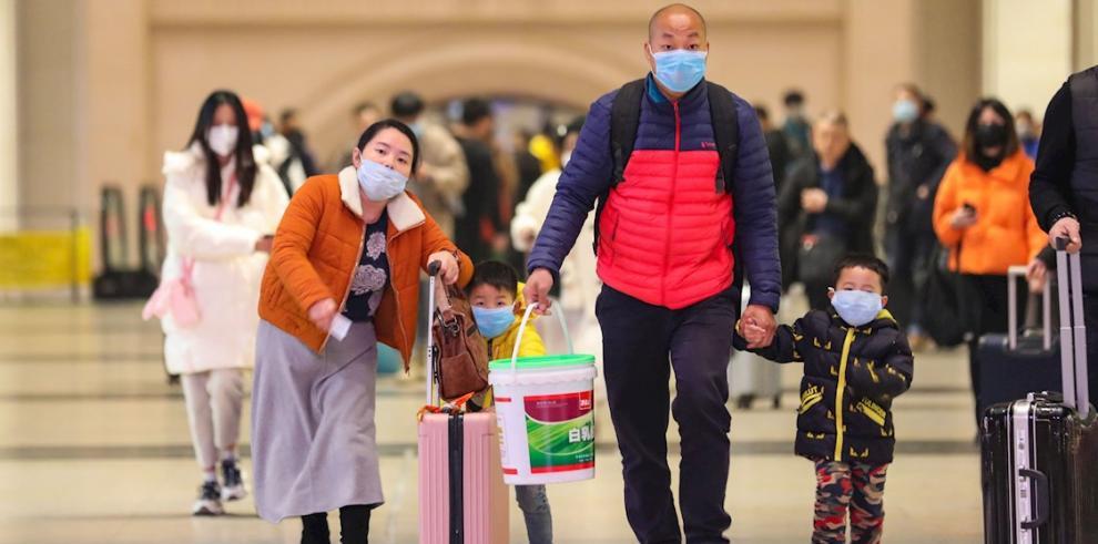 Varios pasajeros se protegen con mascarillas en la Estación de Tren de Hankou en Wuhan, en la provincia de Hubei, China.
