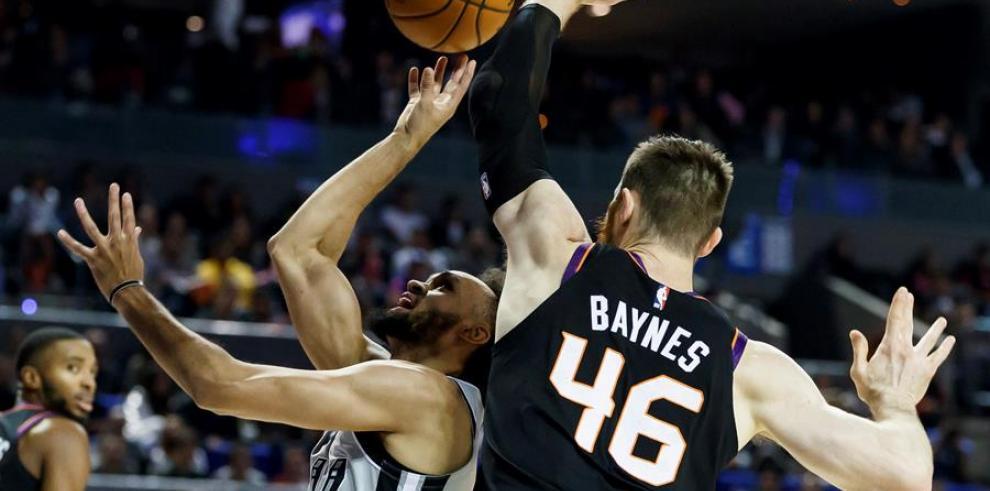 El jugador de los San Antonio Spurs, Derrick White (i) tira a la canasta.