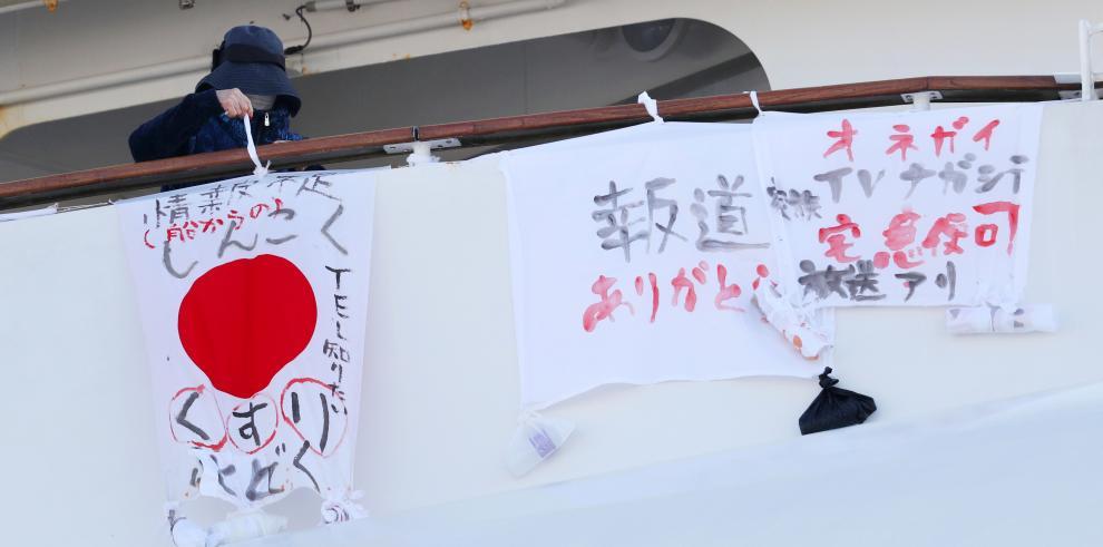 Un pasajero del crucero Diamond Princess cuelga en una cubierta del barco varias pancartas que dicen: grave escasez de medicamentos.