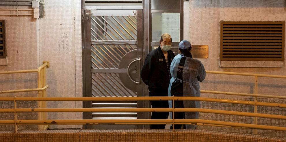 Un residente local habla con un hombre que lleva una bata protectora en las afueras de Hong Mei House en Hong Kong, China.