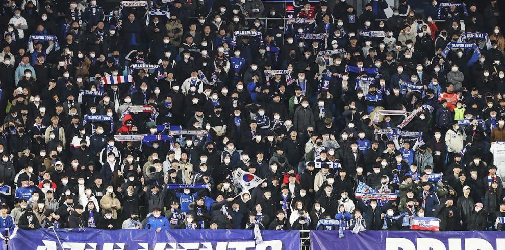 Espectadores se protegen con mascarillas en un partido de fútbol disputado en Seúl.