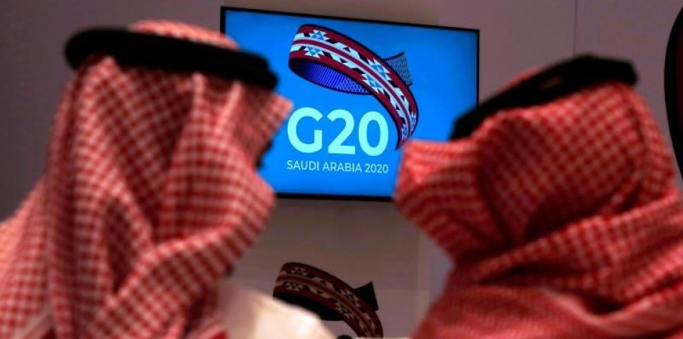 Dos hombres saudíes, sentados frente a un televisor, durante la reunión de ministros de Finanzas y gobernadores de los bancos centrales de los estados miembros del G20 en Riad (Arabia Saudí) este sábado. Los representantes principales de los países del G2