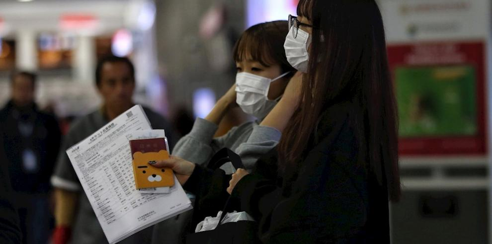 Un grupo de personas usa cubrebocas el miércoles 22 de enero de 2020, durante su arribo al Aeropuerto Internacional de Ciudad de México.