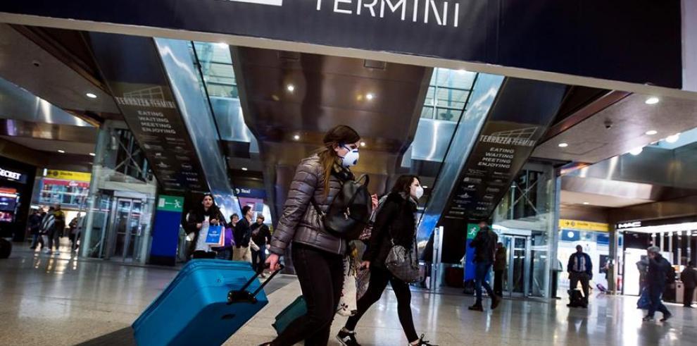 Pasajeros con mascarillas transitan por la estación Termini, en Roma.