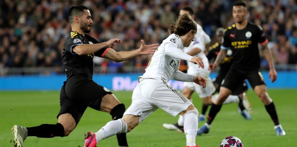 El centrocampista croata del Real Madrid Luka Modric (c) controla el balón ante el centrocampista alemán del Manchester City Ilkay Gubdogan en el partido de ida de octavos de final de la Liga de Campeones que se disputó en el estadio Santiago Bernabéu