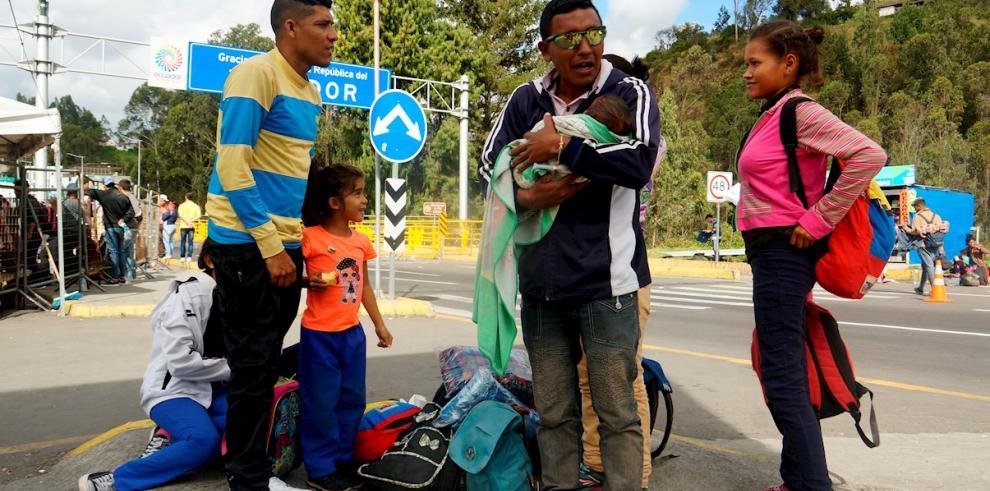 En la imagen, ciudadanos venezolanos descansan luego de cruzar desde Colombia a Ecuador por el puente internacional de Rumichaca.