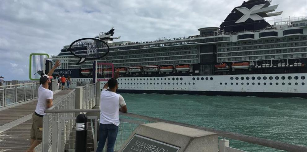 Dos personas saludan hacia un crucero durante su salida del puerto de Miami, Florida (EE.UU.).