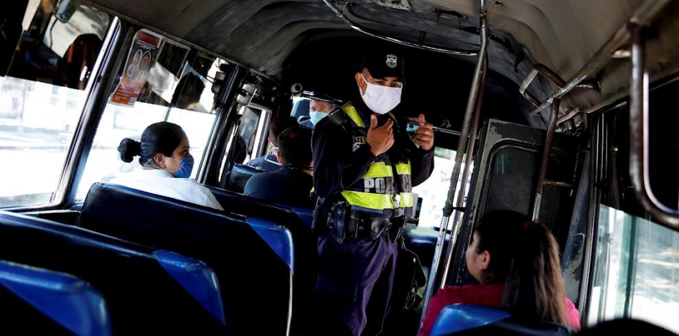 Un agente policial inspecciona que el trasporte público cumpla con normas de seguridad sanitaria en San Salvador (El Salvador).